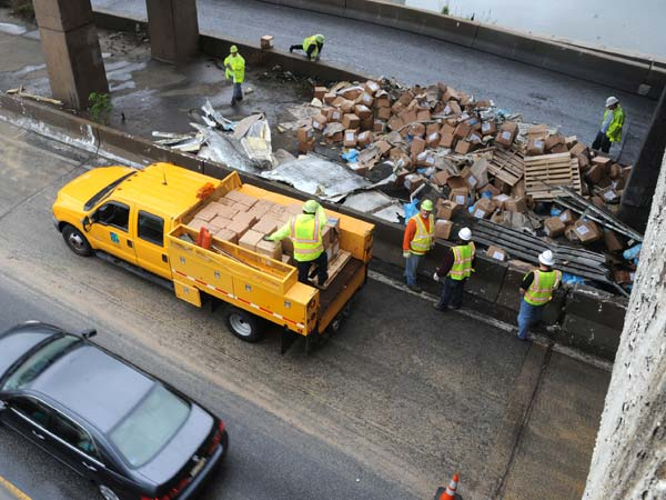 PennDot workers begin the cleanup of a tractor trailer crash on the Schuylkill Expressway westbound at the Vine Street exit May 8, 2013.  The truck lost control and jack-knifed, spilling its load of cartons of cooking grease, which the PennDot workers are loading onto trucks and taking away.  ( CLEM MURRAY / Staff Photographer )