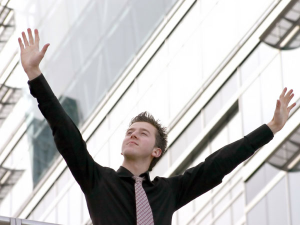 Young business man raising his arms in triumph.