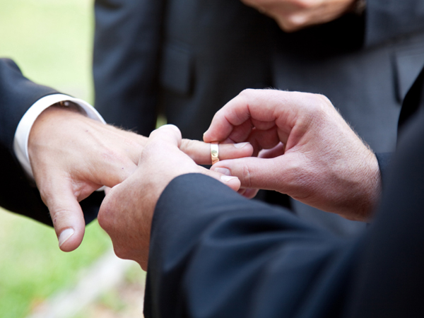 One groom placing the ring on another man´s finger during wedding.