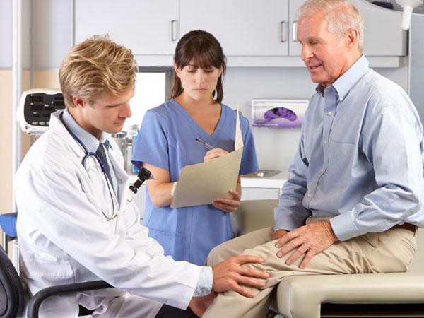Doctor examining man´s knee.