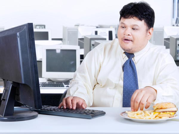 Man enjoys a sandwich and fries at work.
