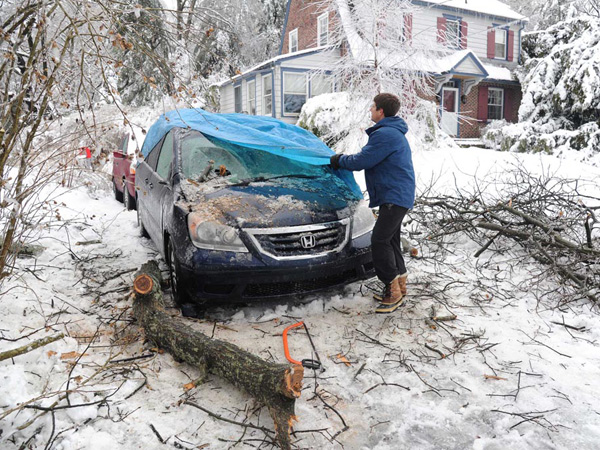 Dave Moffett, 49, covers his minivan with a tarp after a large branch from an oak tree impaled the roof and windshield in his driveway on North Franklin Street near Virginia Street in West Chester on Feb. 5, 2014. An overnight freezing rain storm swept through the Philadelphia region leaving downed trees and power lines in its wake. (CLEM MURRAY / Staff Photographer)