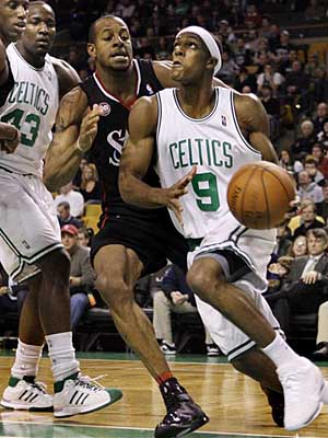 Boston Celtics guard Rajon Rondo (9) drives on Philadelphia 76ers guard Andre Iguodala as Boston Celtics center Kendrick Perkins (43) and Philadelphia 76ers forward Thaddeus Young, far left, look on during the first quarter of their NBA basketball game in Boston Tuesday, Dec. 23, 2008. (AP Photo/Elise Amendola)