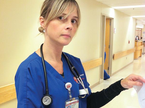 Nurse Marianne Pecora checks patient charts at Temple University Hospital. (Photo by Jane M. Von Bergen)