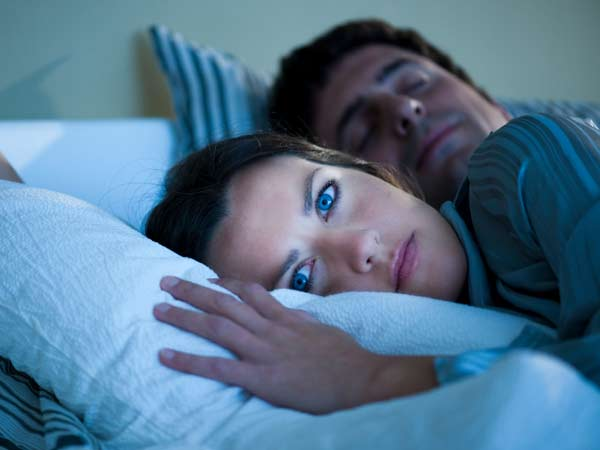 Women suffering from insomnia while her husband sleeps.