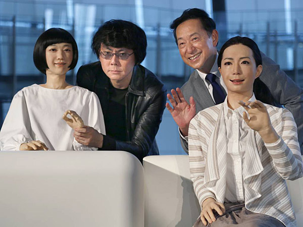 Japanese android expert Hiroshi Ishiguro, second left, and National Museum of Emerging Science and Innovation Miraikan Chief Executive Director Mamoru Mohri, second right, pose with a female-announcer robot called Otonaroid, right, and a girl robot called Kodomoroid during a press unveiling of the museum´s new guides in Tokyo Tuesday, June 24, 2014. The latest creations from Osaka University Prof. Ishiguro are the Otonaroid, the Kodomoroid and Telenoid, a hairless mannequin head with pointed arms that serves as a cuddly companion. The robots with silicon skin and artificial muscles were shown to reporters at Miraikan museum on Tuesday. (AP Photo/Shizuo Kambayashi)