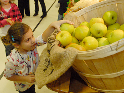 Soffia Woodruff, a first grader at Stockton Elementary School in Cherry Hill, reaches for an apple during a fruit and vegetable wholesaler´s visit. (Ron Tarver / Staff Photographer)