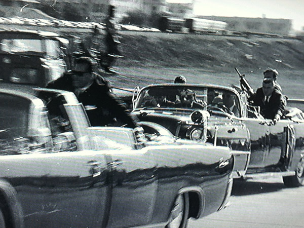 Secret Service agent George Hickey is seen brandishing a rifle as the limousine carrying a wounded President Kennedy, with agent Clint Hill on the back, speeds away from Dealey Plaza in Dallas on Nov. 22, 1963. One theory is that Hickey accidentally shot JFK.