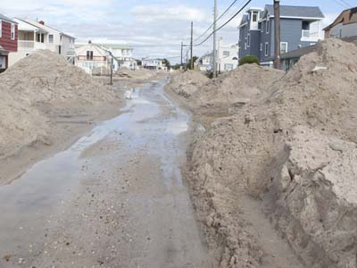 Mountains of sand are plowed along 83rd street in Long Beach Twp. Wednesday, October 31, 2012 in the aftermath of Hurricane Sandy on Long Beach Island. ED HILLE / Staff Photographer