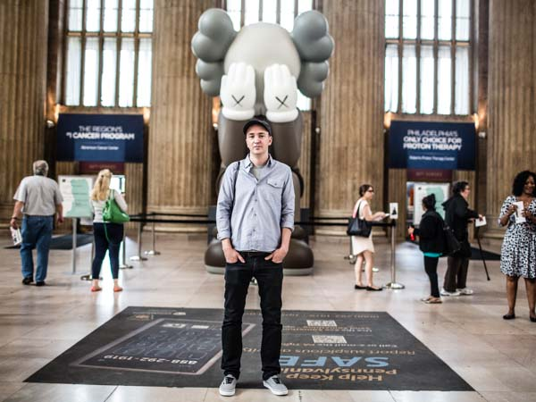 "The artist KAWS stands in front of his ""COMPANION (PASSING THROUGH)"" installation at 30th Street Station in Philadelphia. (Colin Kerrigan/Philly.com)"