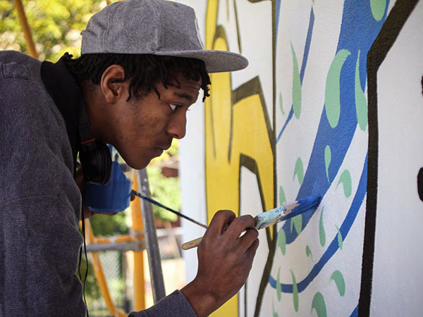 "Malachi Floyd, a restoration assistant, paints the Keith Haring mural on the corner of 22nd and Ellsworth Streets in South Philadelphia on Tuesday, Oct. 21, 2013. ""It is an honor to work on this project,"" Floyd says. (Stephanie Aaronson / Philly.com)"