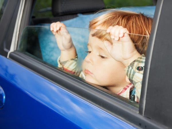 Young boy waits in the car.
