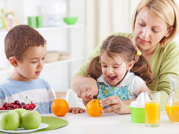 Mother helping her children make some fresh juice.
