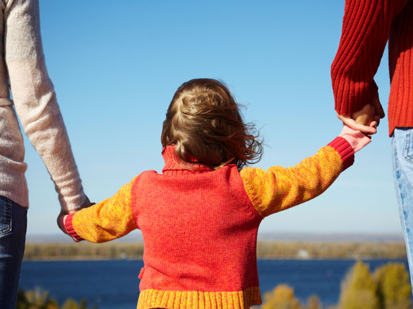 Child holding her parents´ hands.