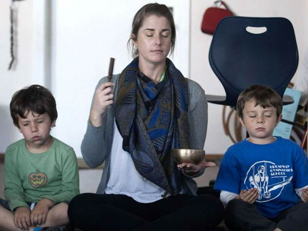 Kindergarten teacher Erica Eihl leads the meditation with Lucas Gold (left) and Husam Arab at Citizens of the World Mar Vista in Culver City, Calif.