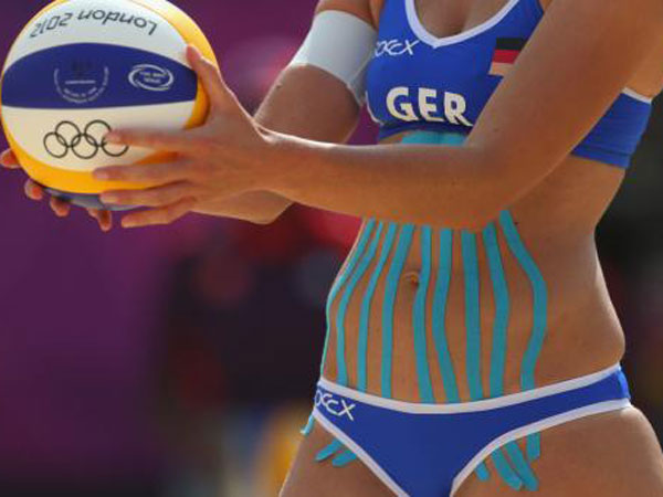 Katrin Holtwick of Germany is taped during the London 2012 Olympic women´s beach volleyball match between Germany and Czech Republic.
