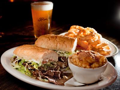 "Sloppy, tender roast beef po-boy with ""debris"" gravy, on genuine Leidenheimer bread from New Orleans, with a pint of Ballast Point Yellowtail ale. (DAVID M WARREN / Staff Photographer)"