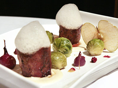 "The ""pork, beans & beer"" features two strikingly smooth pillars of tenderloin atop white-bean puree, with a sudsy toupee of bubbled Guinness. The dish also comes with brussels sprouts, a dehydrated apple chip, dried cranberries, and cranberry and lemon gels. (ELIZABETH ROBERTSON / Staff Photographer)"
