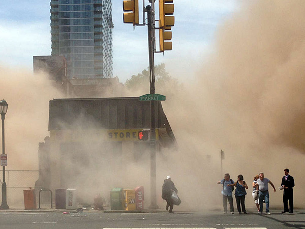 A dust cloud rises as people run from the scene of a building collapse on the edge of downtown Philadelphia on Wednesday, June 5, 2013. Six people were killed after the structure collapsed. (AP Photo/Jordan McLaughlin, File)