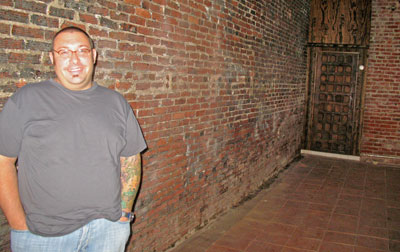 Matt Levin inside the brick-walled space that will become Rubb BBQ, in a horribly lit photo.