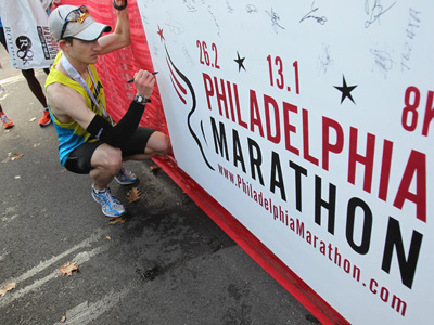 Michael McKeeman was the first to cross the finsih line in the 19th Annual Philadelphia Marathon.  He signs a board with all the winners names. (Charles Fox/Staff)