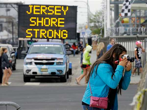 Angelina Zuzuro, 16, of Denville, takes photos near a sign in Seaside Heights, N.J., Saturday, May 18, 2013. (AP Photo)