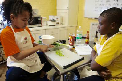 Jayla Baxter dices celery while Alhaji Saccoh waits his turn. The students are preparing turkey sloppy joes and quick pickles as part of the Spring 2016 My Daughter's Kitchen cooking program at Philad