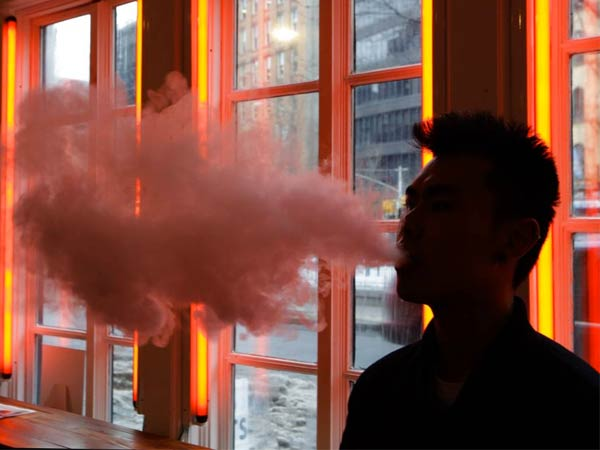 "In this Feb. 20, 2014 photo, a patron exhales vapor from an e-cigarette at the Henley Vaporium in New York. the proprietors are peddling e-cigarettes to ""vapers"" in a growing movement that now includes celebrity fans and YouTube gurus, online forums and vapefests around the world. (AP Photo/Frank Franklin II)"