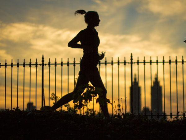 A woman goes for a run during sunset.