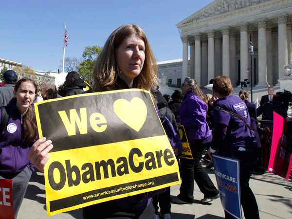 "File photo: Holding a sign saying ""We Love ObamaCare,"" a supporter of health care reform rallied in front of the Supreme Court in Washington, Tuesday, March 27, 2012. (AP Photo/Charles Dharapak)"