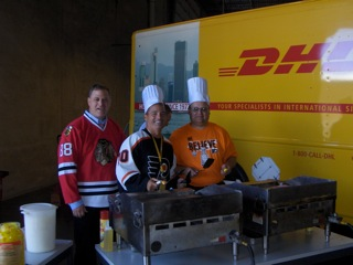 Al Burba (center) with DHL colleagues John Marchese Sr. (left) and Robert Murray working the grill Monday in Chicago.