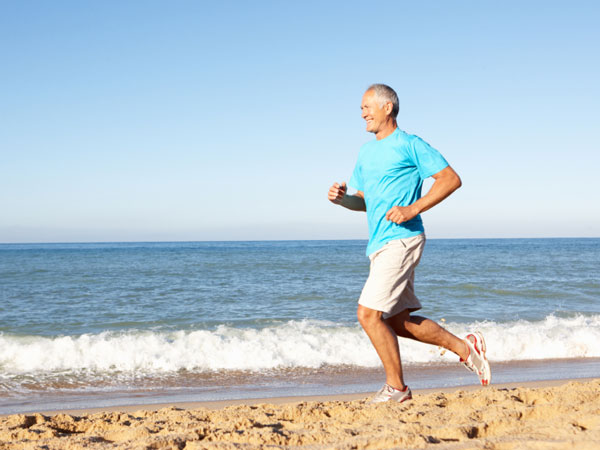 Older man running on the beach.