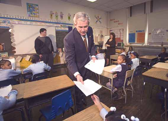 During his visit to Kearney Elementary School, President Bush collects papers from students in Cheryl Feldscher´s second grade class.Here he prepares to take a paper from Sharrell Lewis. (Ed Hille / Staff Photographer)
