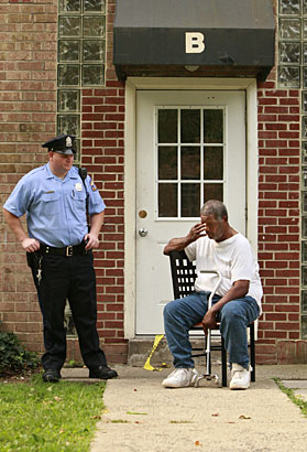As a police officer keeps the entrance secure, William Outlaw sits outside his niece´s apartment building after she was found murdered inside her Fairmount Manor apartment. (Elizabeth Robertson / Staff Photographer)