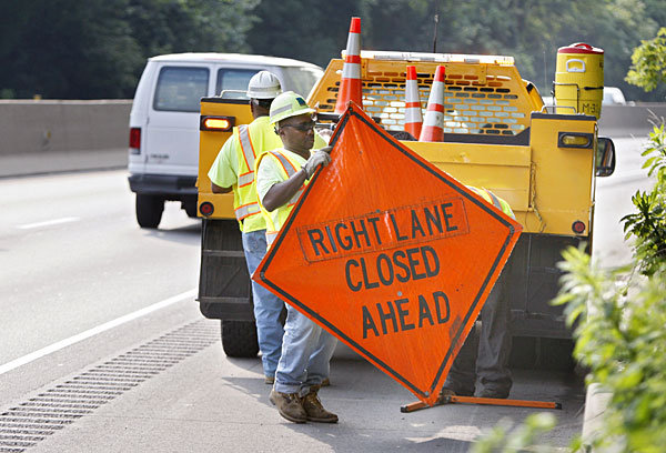 On the eastbound Schuylkill Expressway at the Conshohocken curve, PennDot equipment operator John Anderson of Norristown puts up a sign in preparation for the closure of the right lane of the expressway for storm cleanup.