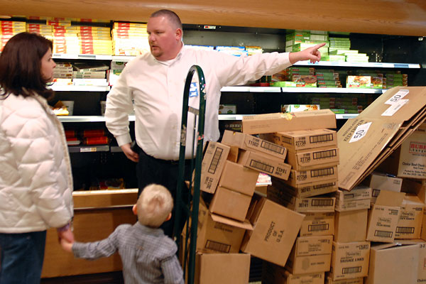 Kevin Russell, manager of the Wegman´s store in Downingtown, interrupts his shelf stocking to give directions to Jen McSherry of Downingtown, shopping before the big storm her son Ryan. (Tom Gralish / Staff Photographer)