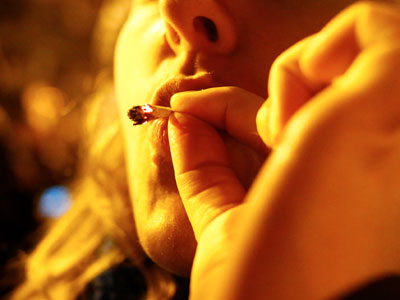 A 30-year-old woman smokes marijuana at a street party after I-502 was approved Tuesday, Nov. 6, 2012, in Seattle&acute;s Capitol Hill neighborhood.  Initiative 502 decriminalizes the possession of up to an ounce of marijuana beginning Dec. 6. (AP Photo/The Seattle Times, Erika Schultz) 