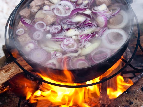 Cooking soup over an open flame.
