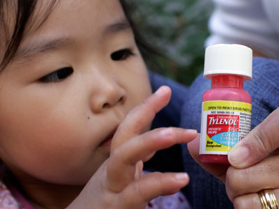 Carleen Ho holds a bottle of Concentrated Tylenol Infants´ Drops Plus Cold & Cough in front of her daughter, Rachel Ho, who is under two years old, at a home in Palo Alto, Calif., Thursday, Oct. 11, 2007. Cold Drug makers voluntarily pulled cold medicines targeted for babies and toddlers off the market Thursday, leaving parents to find alternatives for hacking coughs and runny little noses just as fall sniffles get in full swing. The move represented a pre-emptive strike by over-the-counter drug manufacturers - a week before government advisers were to debate the medicines´ fate. But it doesn´t end concern about the safety of these remedies for youngsters. (AP Photo/Paul Sakuma)