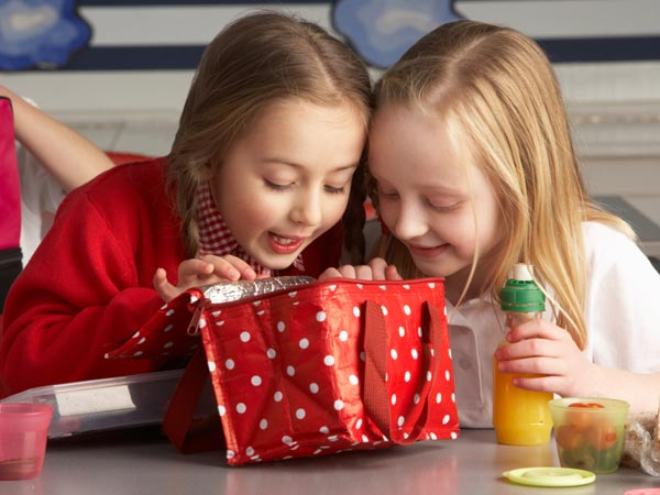 Two girls searching through a packed lunch.