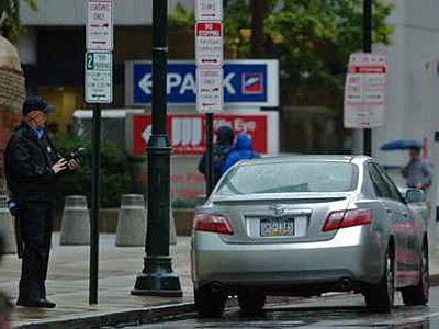 A Philadelphia Parking Authority officer writes a ticket in this file photo. (John Costello / Staff Photographer)