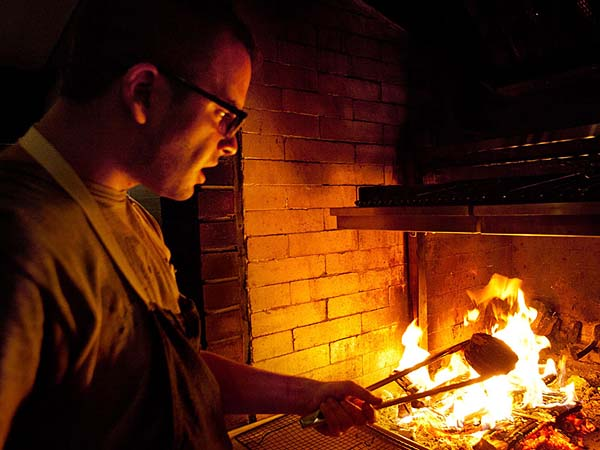 Justin Petruce, co-owner of Petruce et al., at the seven-foot oval wood-fired hearth and grill at the root of the deep flavors at the Walnut Street restaurant.
