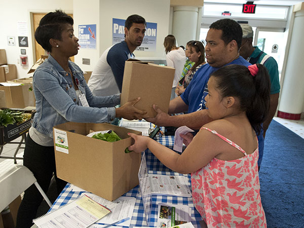 Amba Kasongo, with St. Christopher´s Hospital for Children Farm to Family program, hands Lauro Melendez and his daughter Jessica, 9, a box of food after they signed up for the program at the hospital. (  RON TARVER / Staff Photographer )