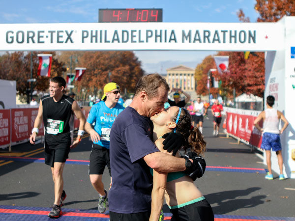A couple kisses after finishing the  Gore-Tex Philadelphia Marathon on Sunday, November 17, 2013. (Stephanie Aaronson / Philly.com)