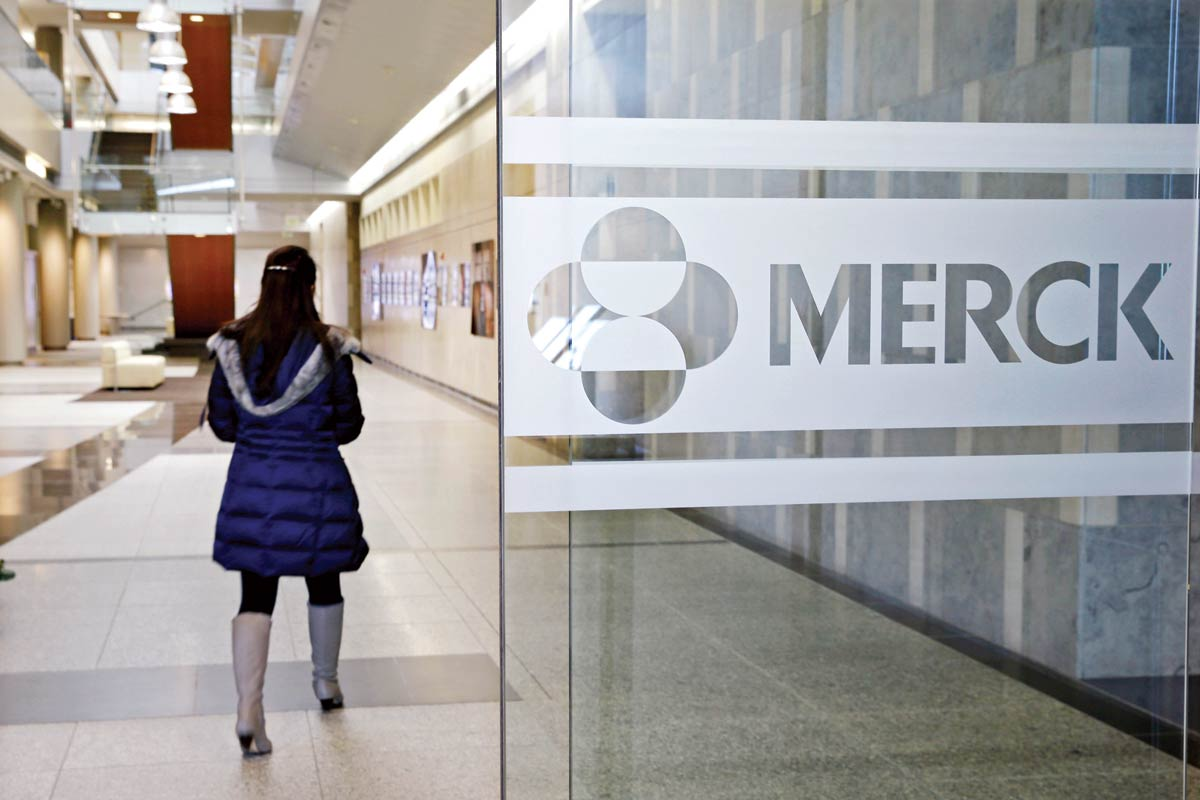 In this Thursday, Dec.18, 2014, photo, a person walks through a Merck & Co. building in Kenilworth, N.J. Merck systems were subject to a ransomware attack this morning and the company and employees were advised to disconnect their computers and avoid talking to the media.