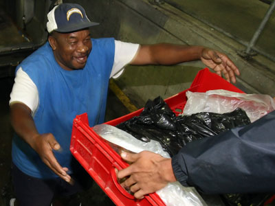 Philadelphia Brotherhood Mission Ministries member Butch Washington is handed a basket of food from member Juan Medina at the loading dock of Citizen Bank Park. (Steven M. Falk / Staff Photographer)