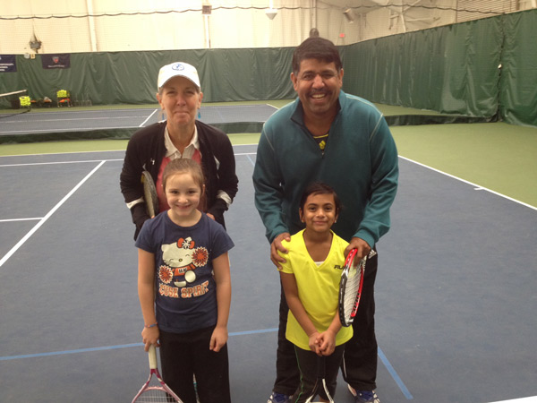 Seven-year-olds Oviya (right) and Katrina (left) learn from tennis professional Suzanne Barr and Director of Tennis Arvind Aravindhan.