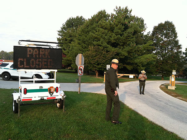 Chief Ranger Gregg Tinkham, left, and Law Enforcement Ranger Trevor Blasco monitor the front gate at Valley Forge National Park, letting guests know that the visitors center, trails, roads and facilities are closed. (Mari Schaefer/Staff)