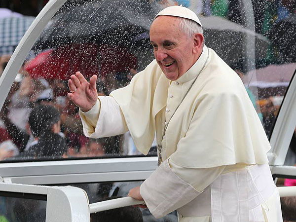 Pope Francis waves to people from his popemobile in Rio de Janeiro, Brazil, Saturday, July 27, 2013. (AP Photo/Andre Penner)