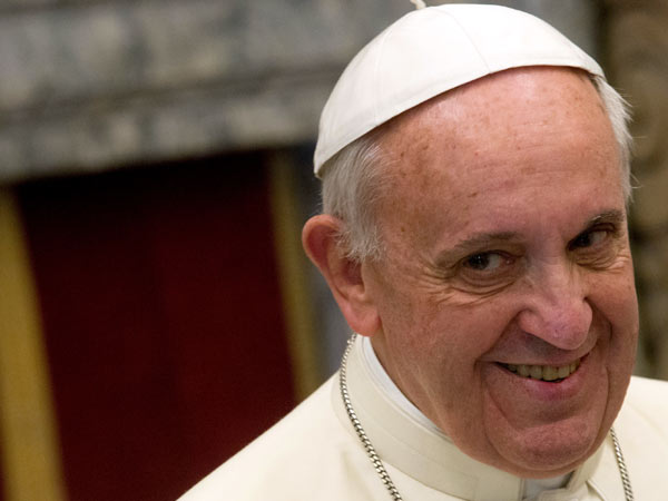 Pope Francis smiles as he addresses the Vatican Curia, in the Clementine hall, at the Vatican, Saturday, Dec. 21, 2103. (AP Photo/Claudio Peri, Pool)